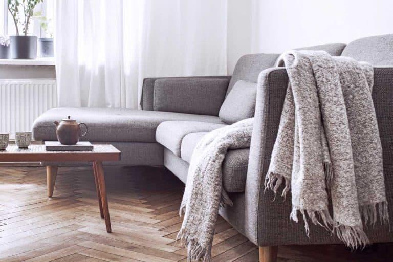 Stylish scandinavian interior of living room with throw drape on sofa