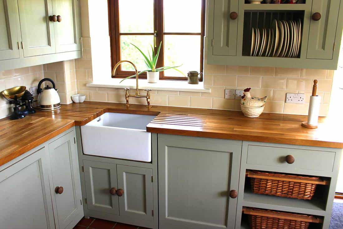 Traditional-country kitchen interior with kettle, wooden-worktops and butler sink