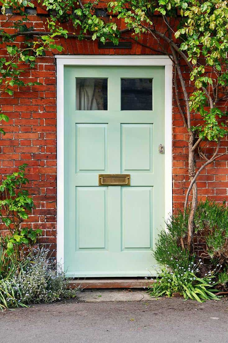 View of a beautiful light green front door of a red brick house