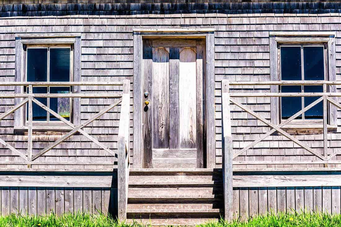 Vintage wooden house with door porch entrance in idyllic rural countryside in summer