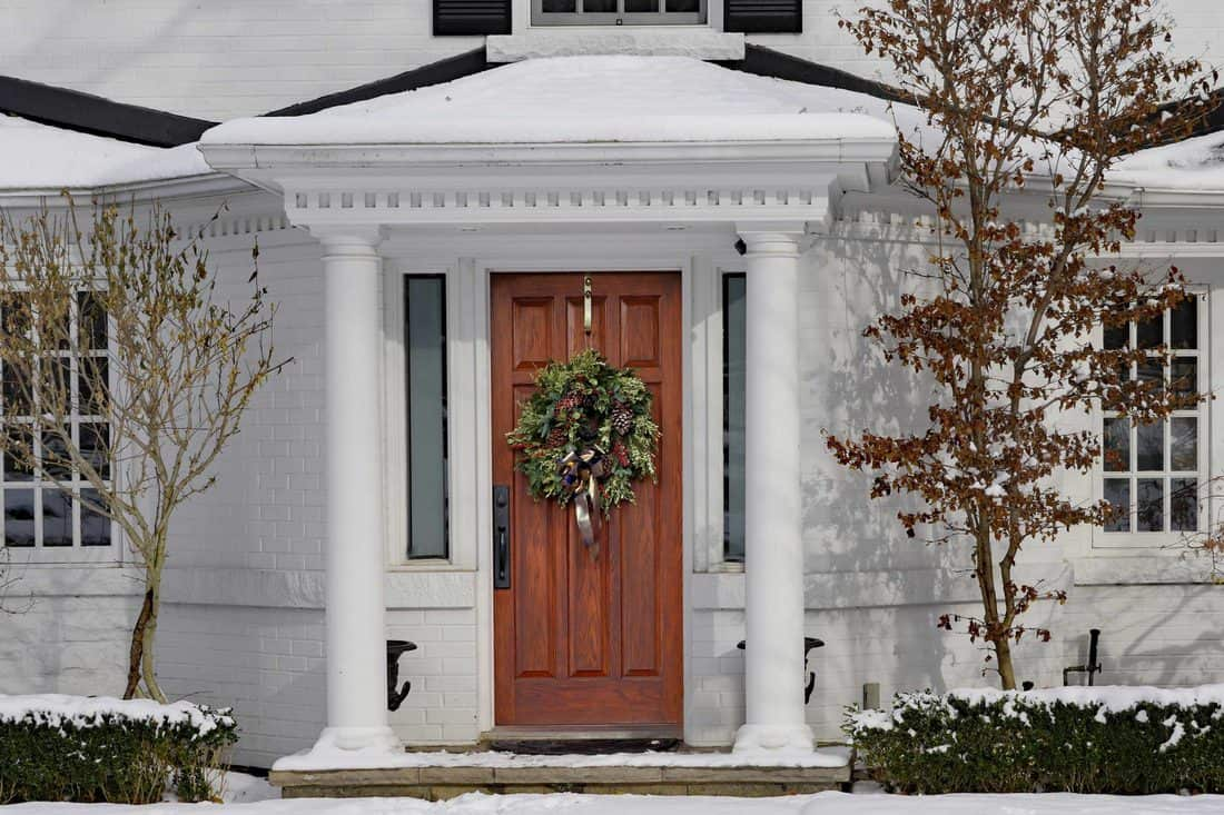 White colored facade with brown door with wreath attached to it