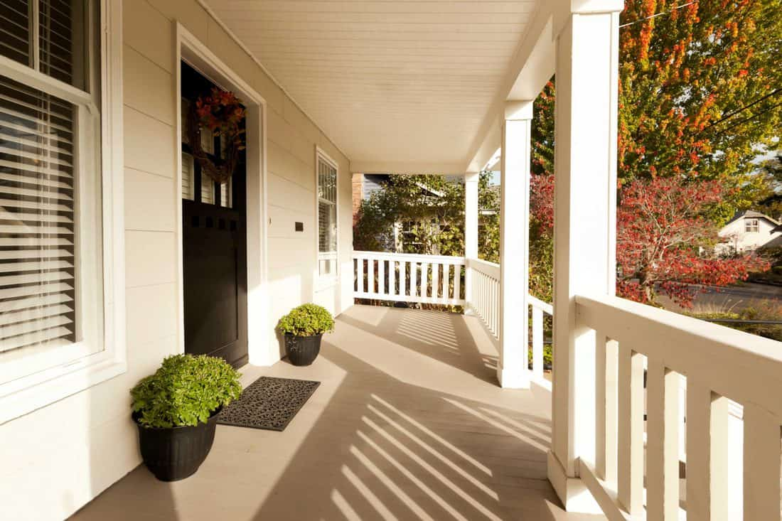 White colored porch with big black door with window and decorative plants on side