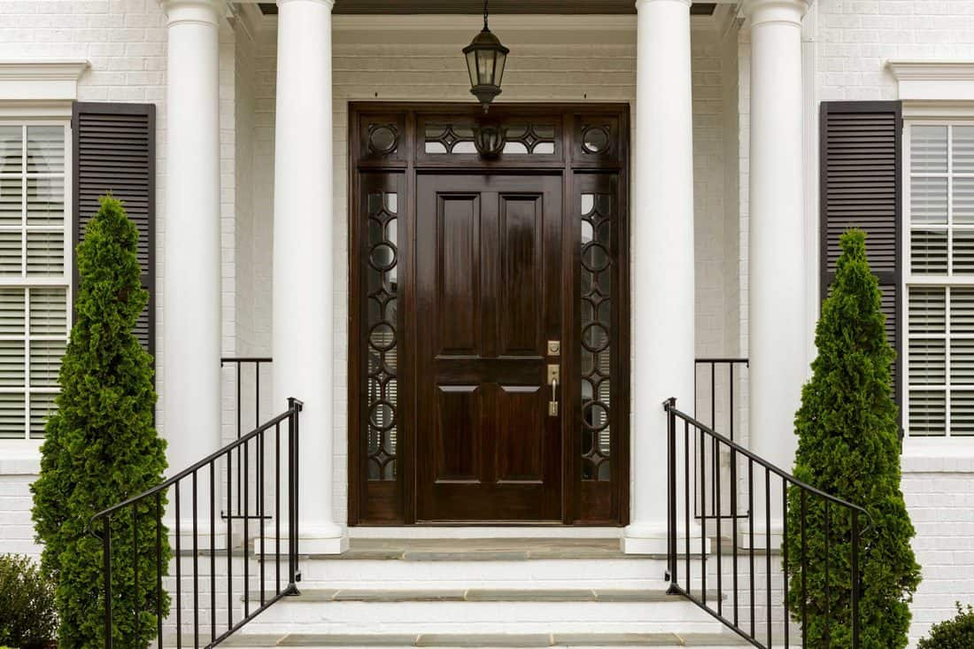 White colored porch with circular columns and black door