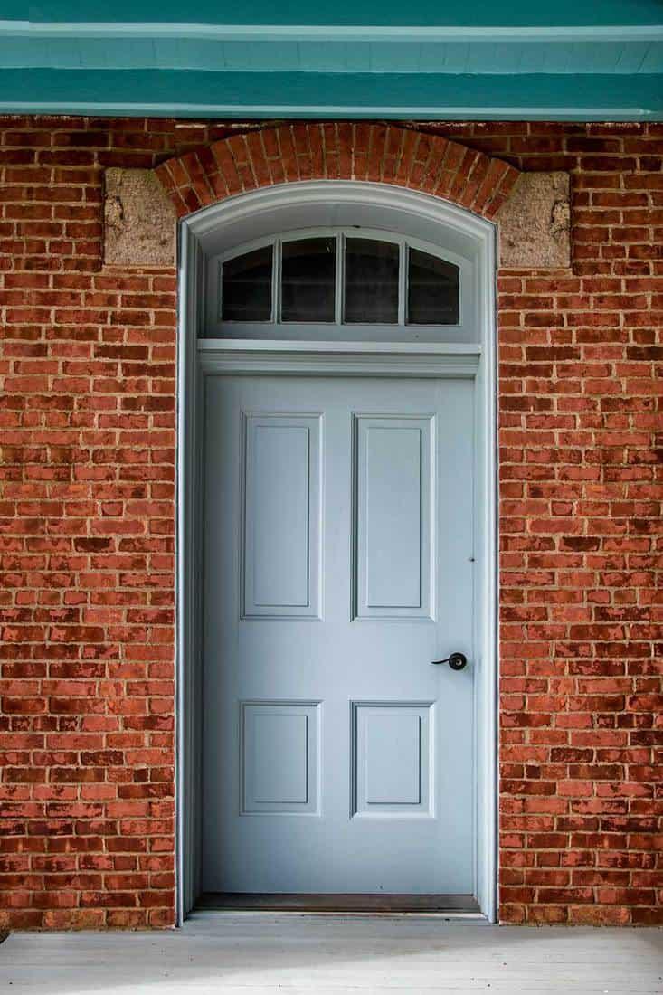 White door on a brick home