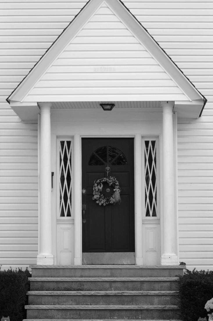 White entry hall with black door and wreath attached to it