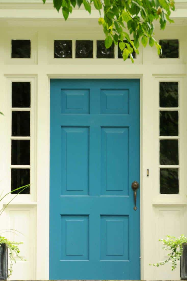 White framed door way and blue door with rectangular groove design