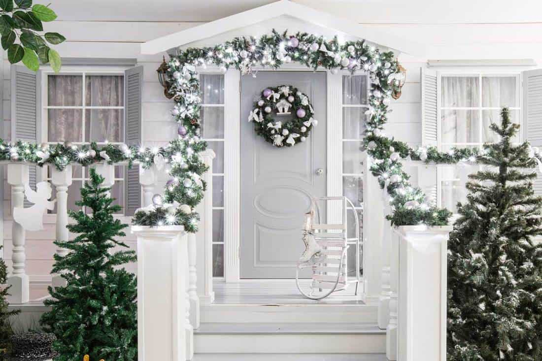White themed facade with christmas trees and wreath decoration on front door