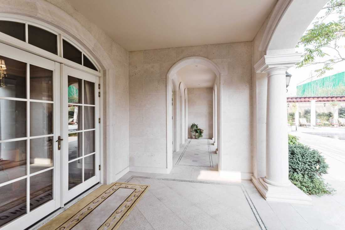 White themed porch with french door with huge window and arched header