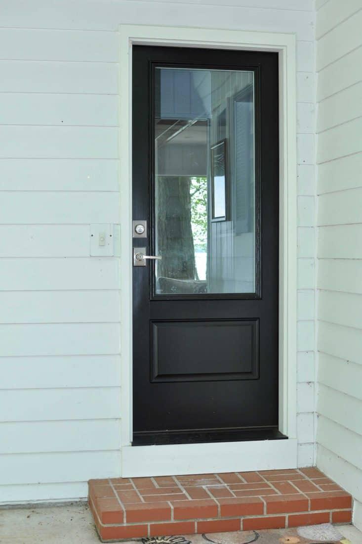 White wall and black door with huge window