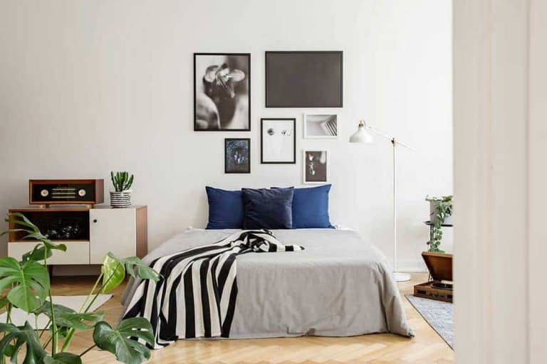 White wooden commode next to bed with dark bluepillows grey duvet and striped black and white blanket in bedroom with framed art gallery on the wall