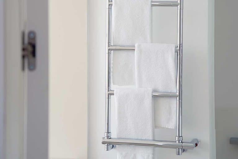 White towels on a chromed heated towel rail in the bathroom