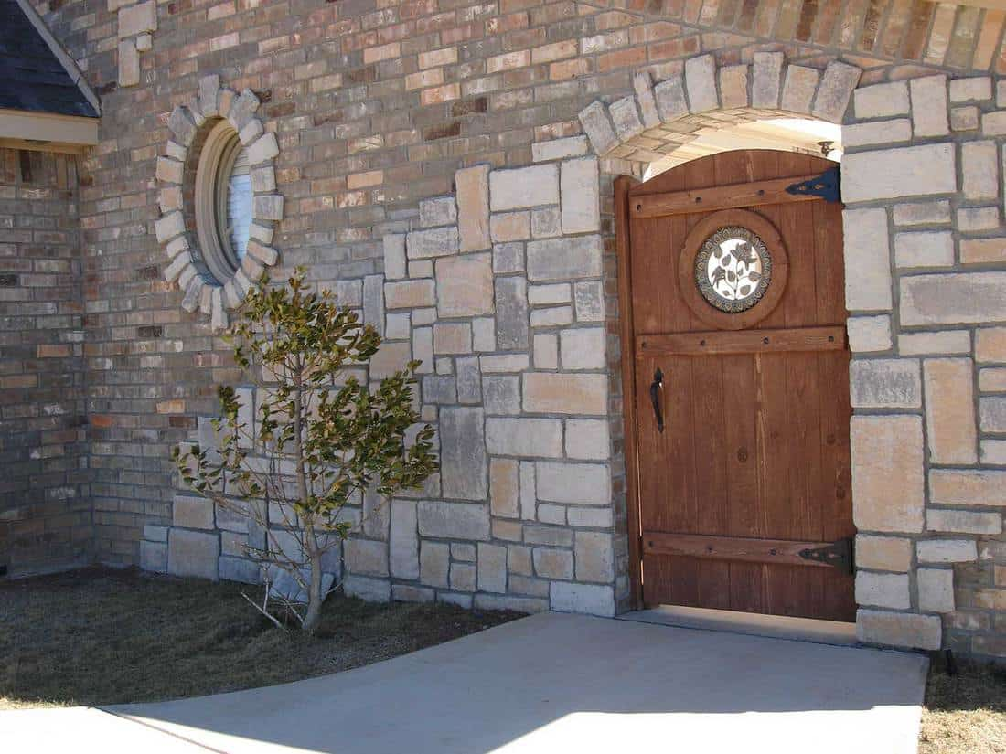 Wood gate in stone and brick walls
