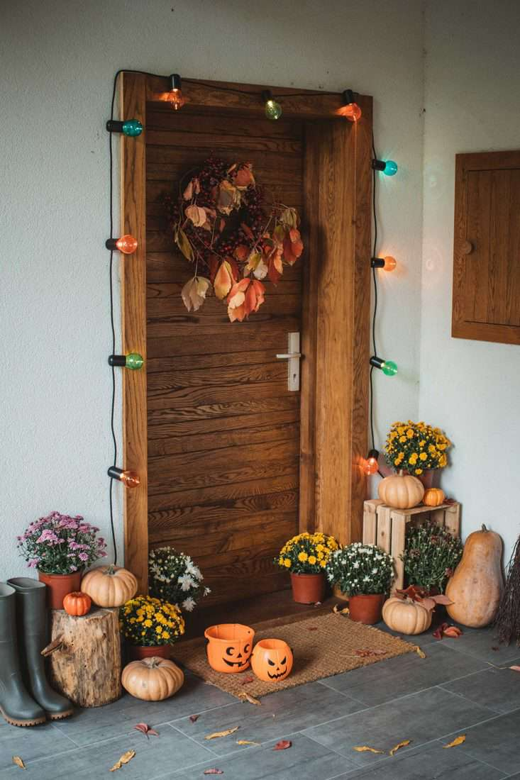 Wooden door with fall decorative leave light decorations and small pumpkins with jack'o lantern baskets