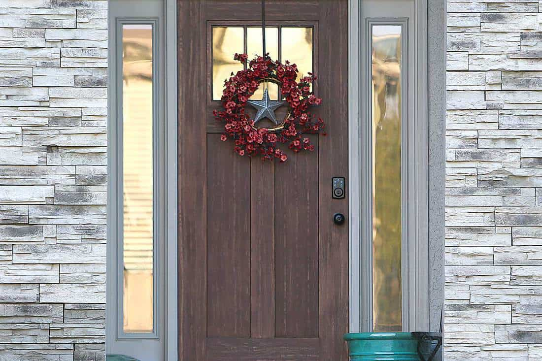 Wooden front door with wreath of a rustic farmhouse with white walls