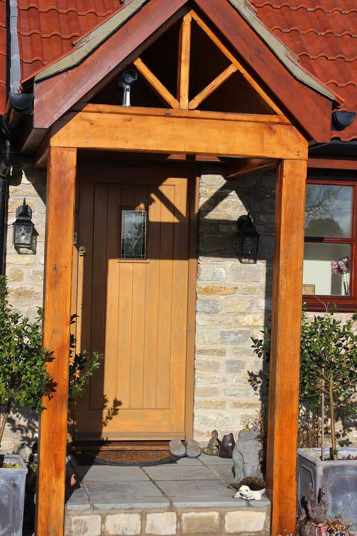 Wooden open porch and front door with a hidden security camera