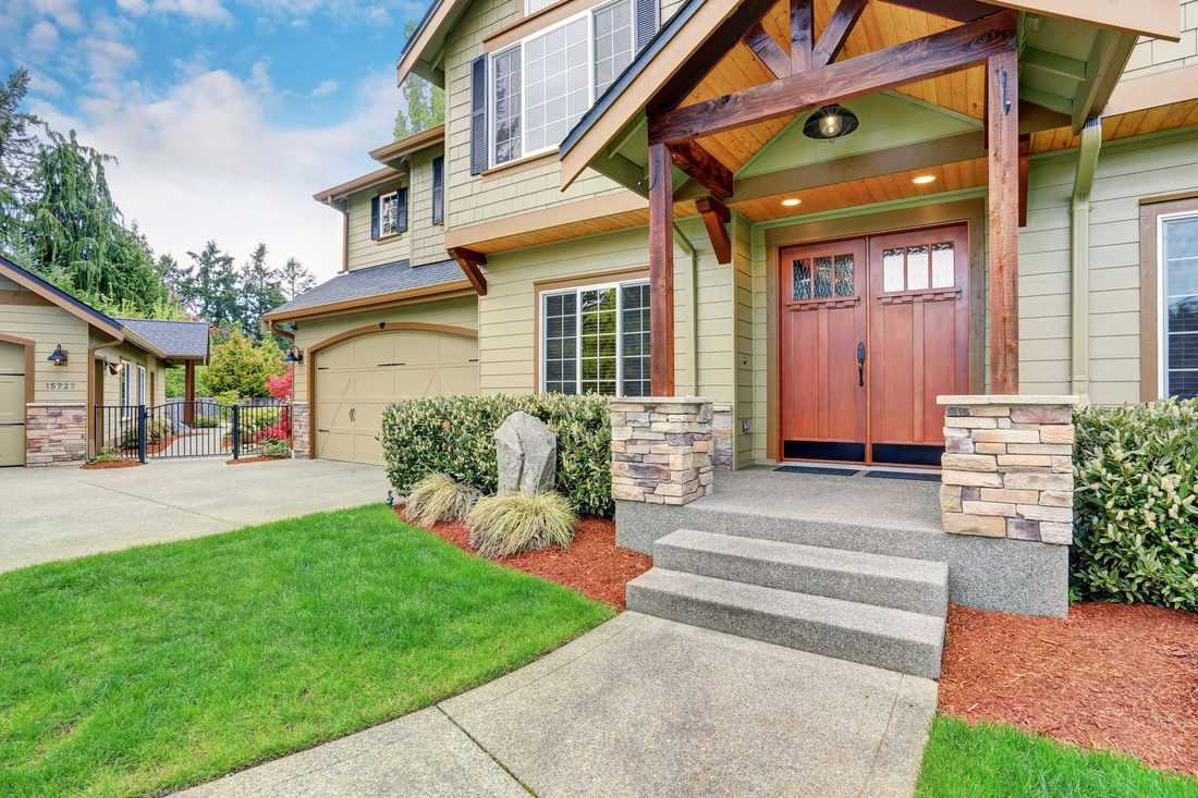 Wooden themed porch with brown french door and huge windows at ground and second floor