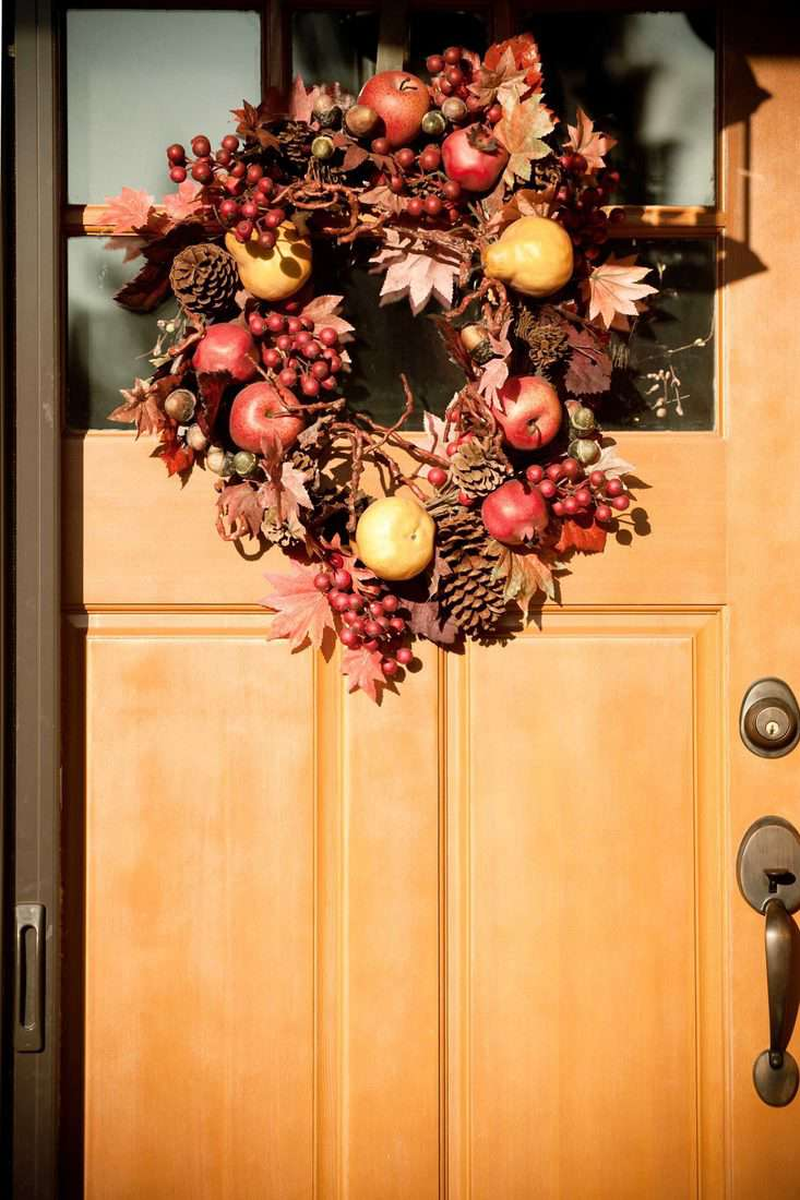 Wreath made with apples, pine cones, blueberries, pears, and leaves attached in front door