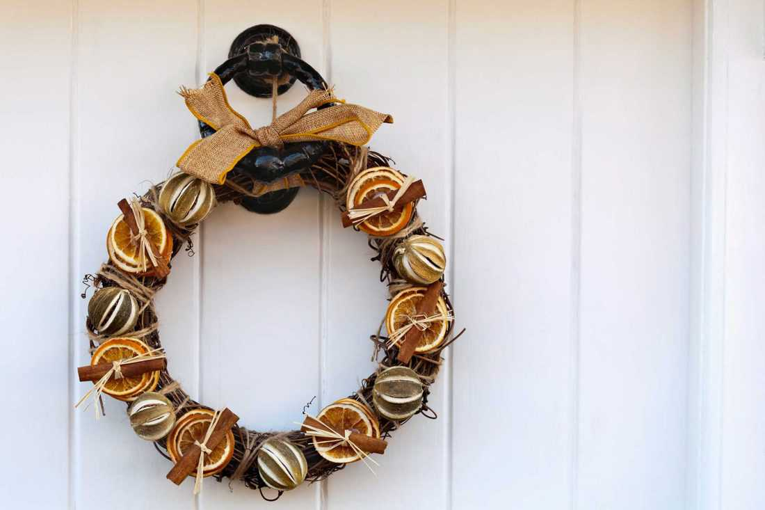 Wreath made with orange slices and twigs attached at door knob