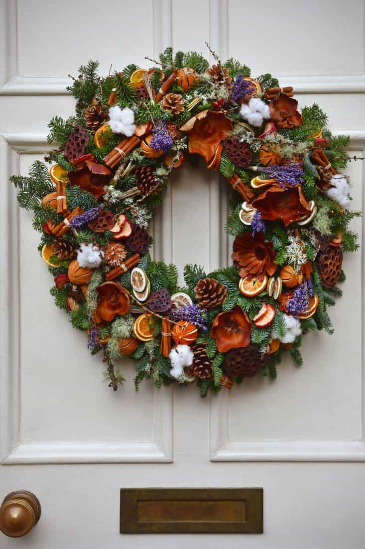 Wreath with orange slices, pine cones, and purple leaves hanging in-front of white door