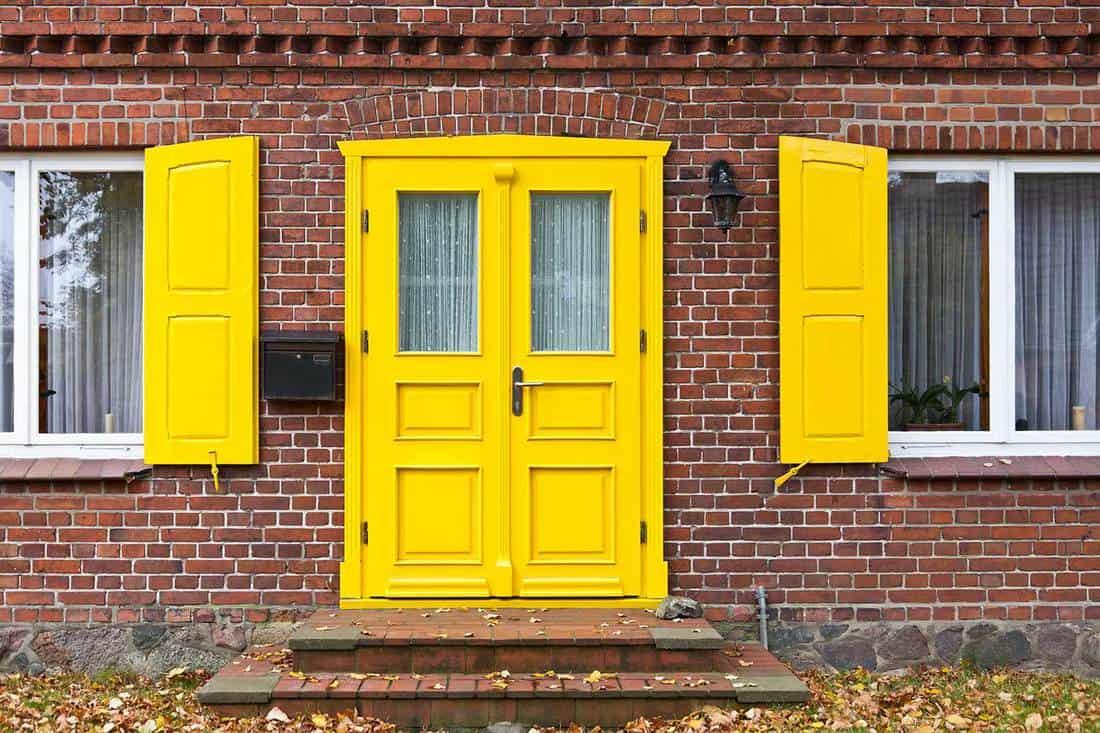 Yellow front door of a brick house