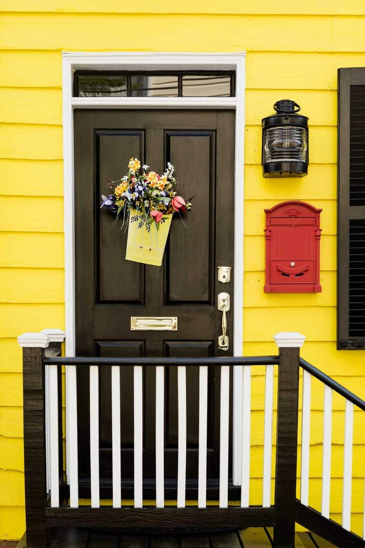 Yellow wooden walls with black and white painted stairway leading to black door with flower decorations