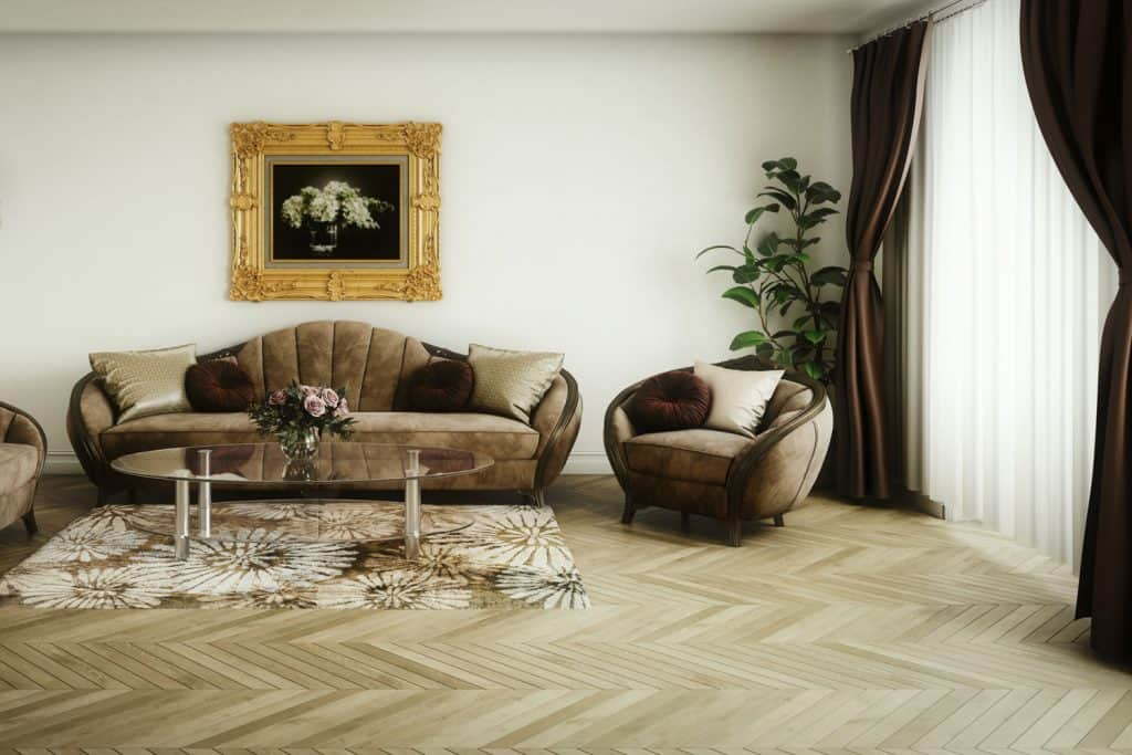 A dark and warm living room with brown sleeper sofas, pattern flooring, floral carpet with a tall coffee table on top, and a dark brown colored curtain