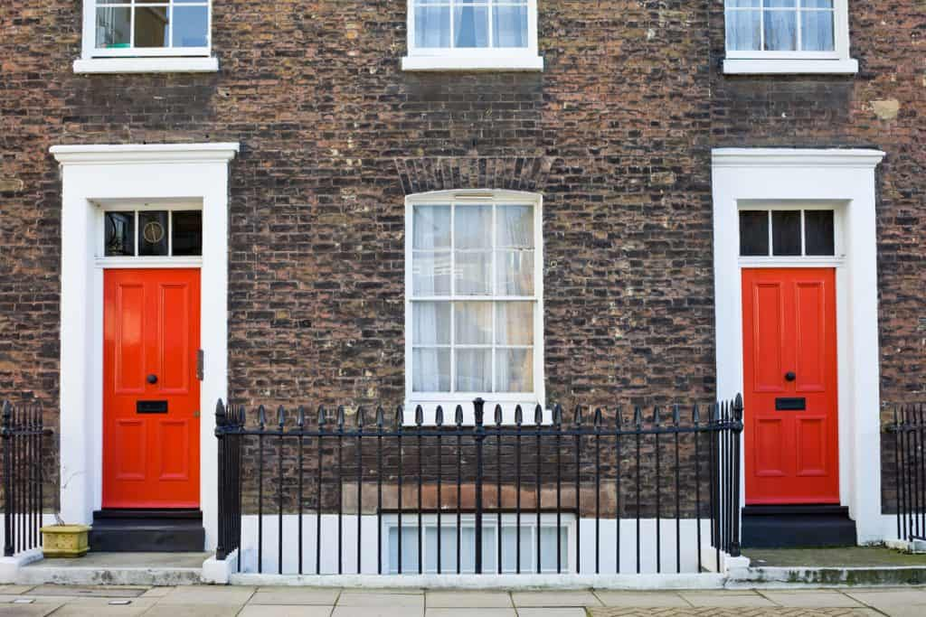 A brick walled apartment with white painted door casing and red painted front doors