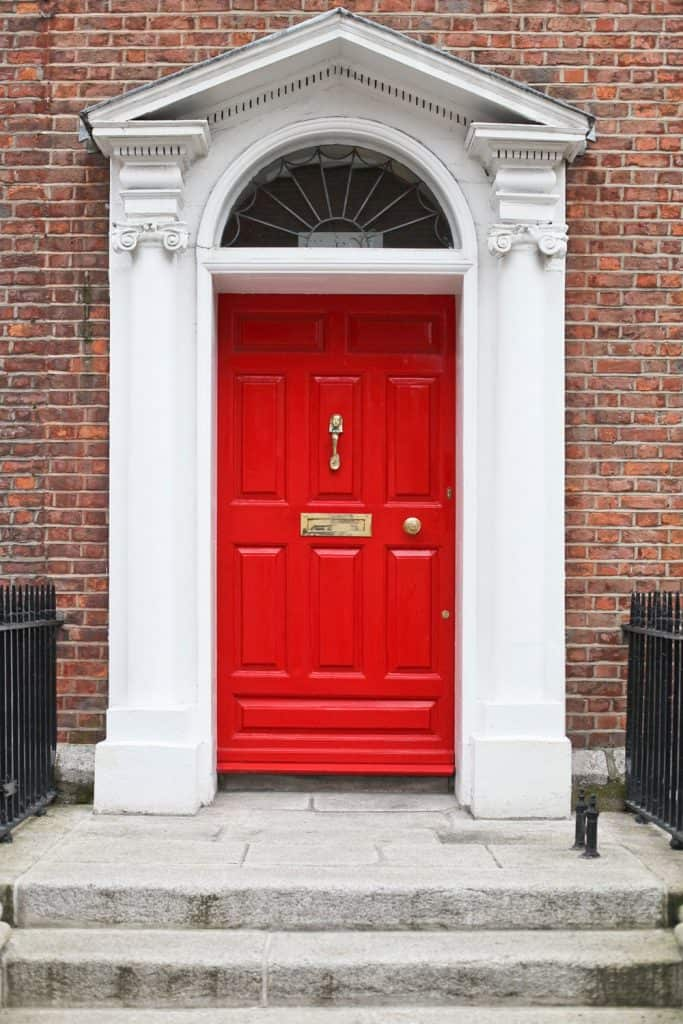 A gorgeous brick and white painted roman pillar entryway with a red front door