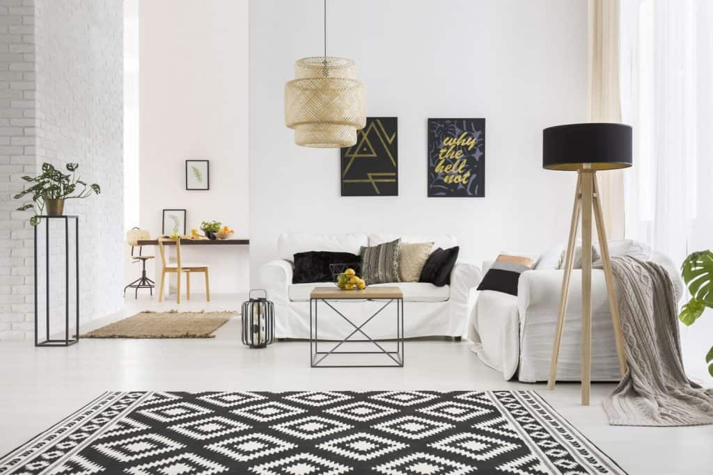 A gorgeous white living room with a patterned black and white rug, white sectional sofa, and picture frames on the wall