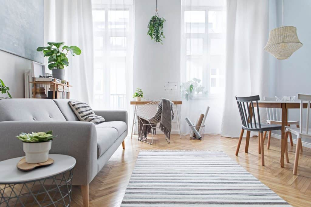 A minimalist themed living room with tiled flooring, striped rug, gray couch, indoor plants all over the living room, and white curtains