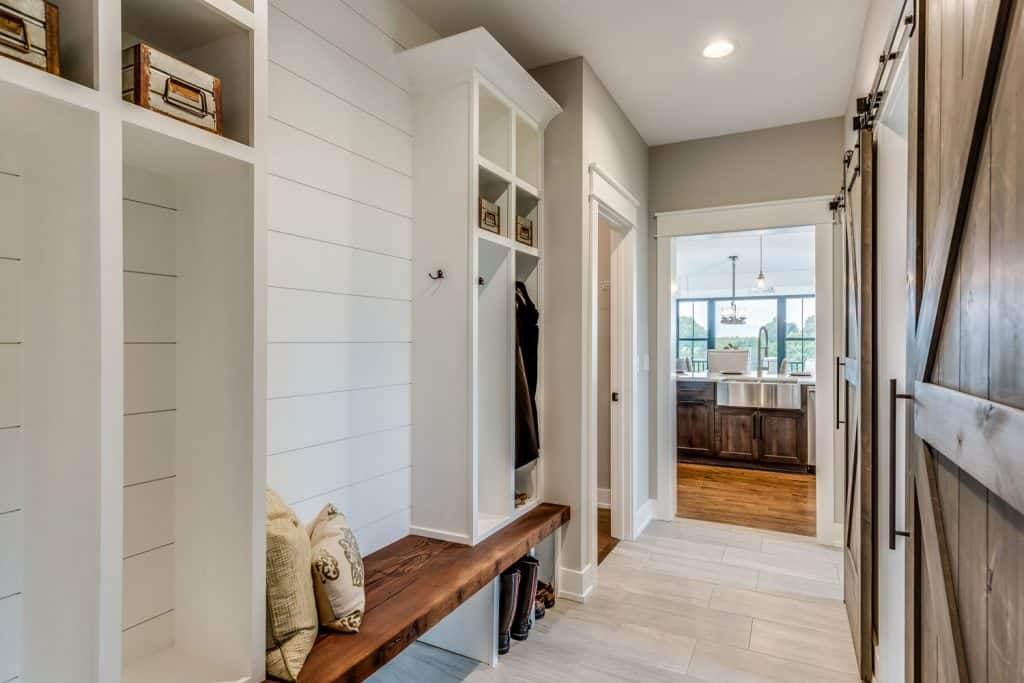 A mudroom with shiplap wall and white painted cabinets