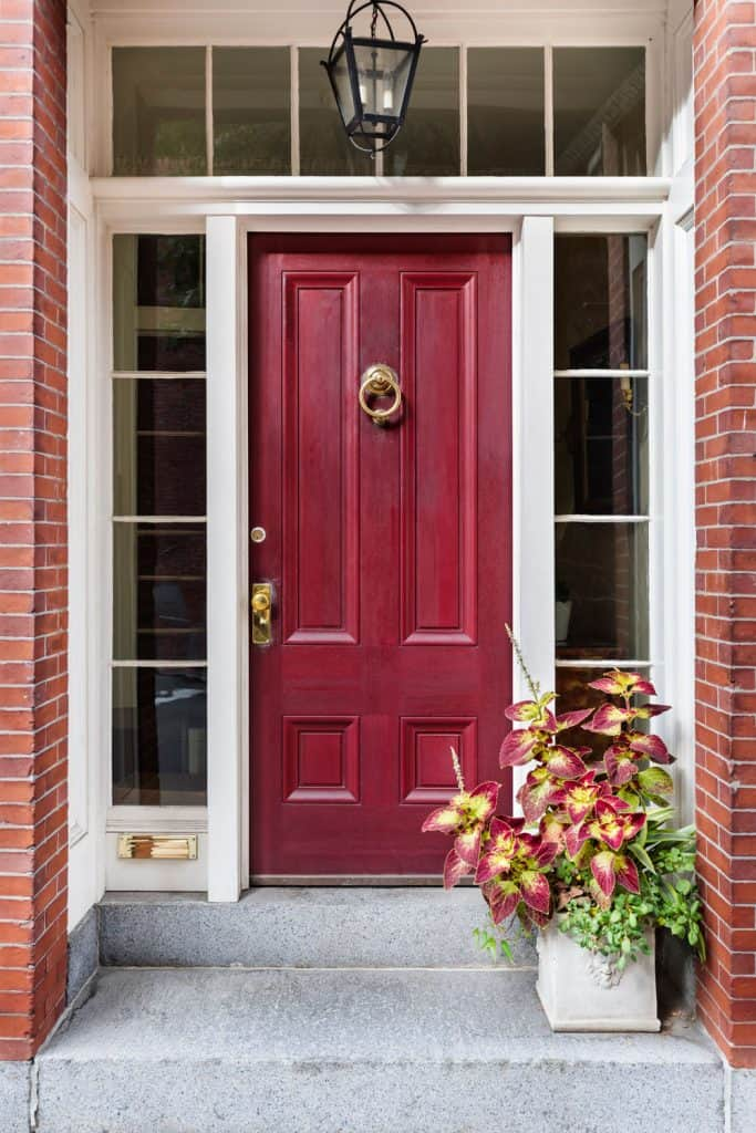 A red front door with white painted window panel frames and a brick design wall