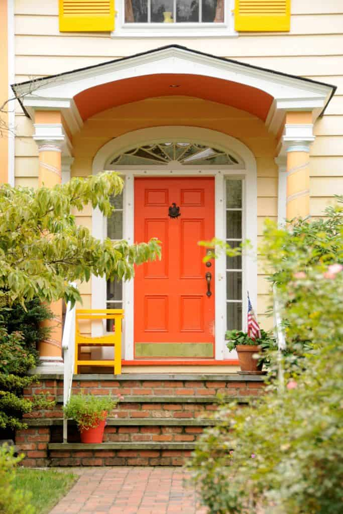 An orange front door with a bifold canopy on the entryway and brick layers steps