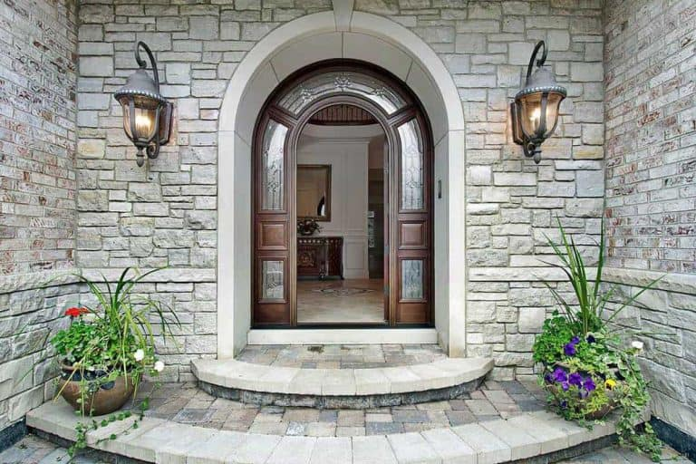 Arched stone entry of luxury suburban home with timber door, Best Front Door Colors For A Gray House