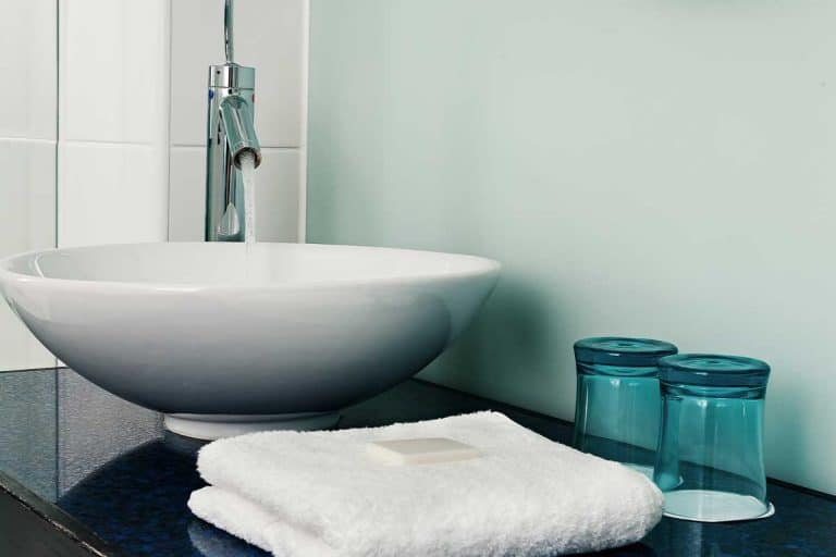 Bathroom sink counter with white towels and blue water glass