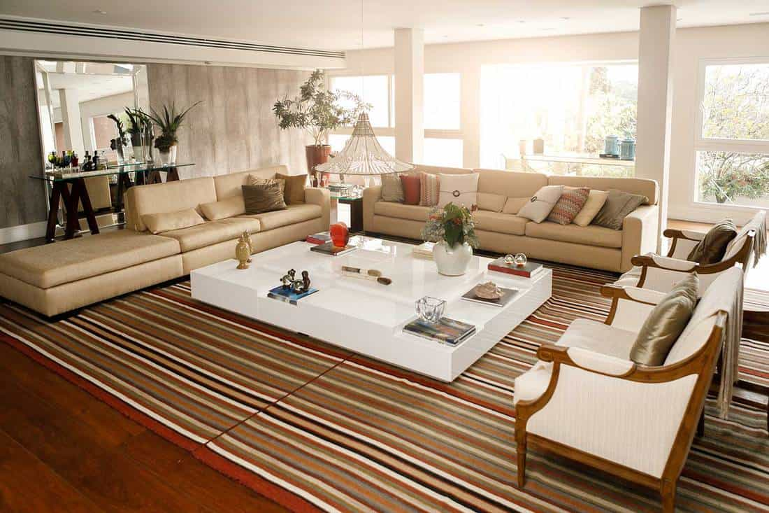 Beautiful large living room with beige sofa, accent chairs, mirror, hardwood floor and large white center table