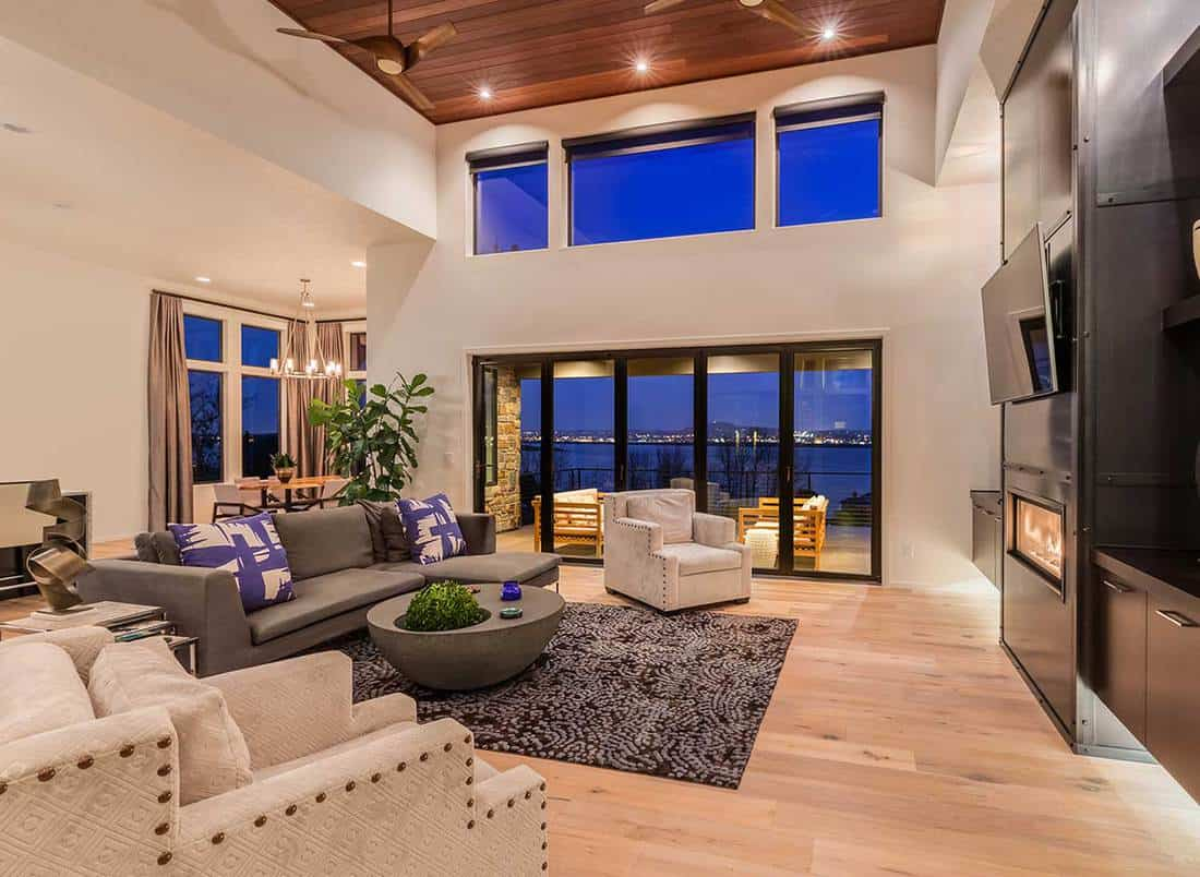Beautiful living room in luxury home with hardwood floors and amazing view of the sea and the city lights at night