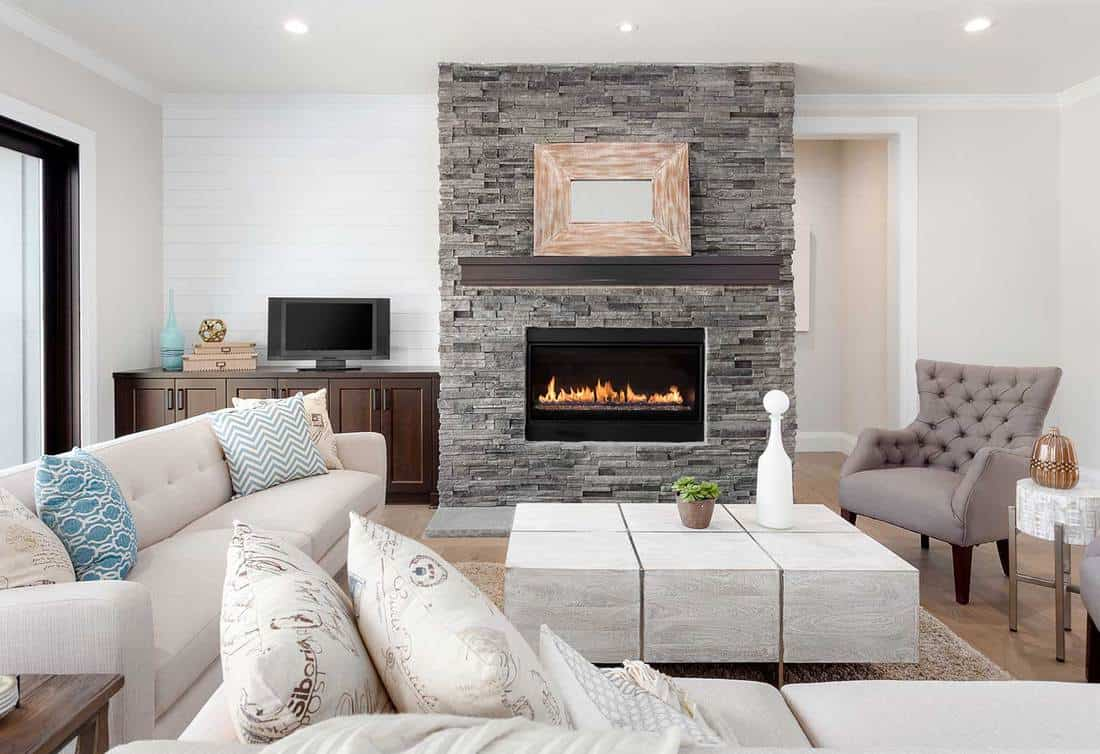 Beautiful living room interior with cozy sofas, hardwood floors and fireplace