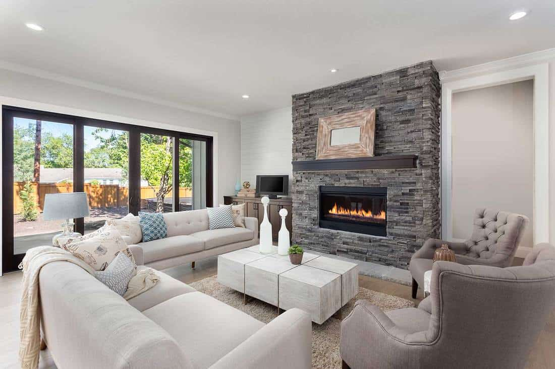 Beautiful living room interior with hardwood floors, modern brick fireplace, cozy sofa set and luxury wooden center table