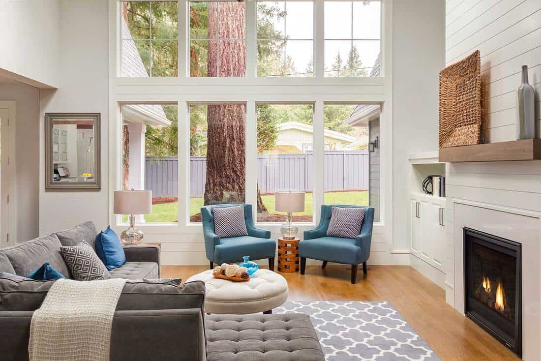 Beautiful living room interior with tall vaulted ceiling, hardwood floors, fireplace, gray sofa and large bank of windows in new luxury home