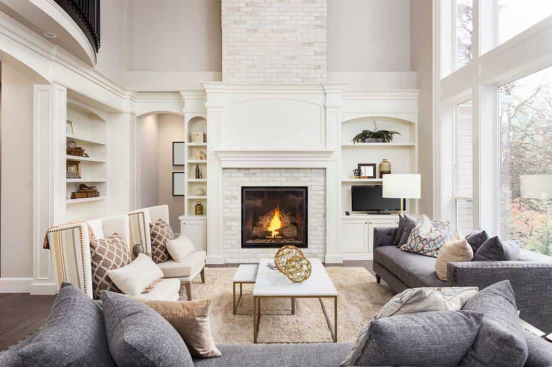 Beautiful living room interior with tall vaulted ceiling, large windows, hardwood floors, cozy gray sofa and fireplace
