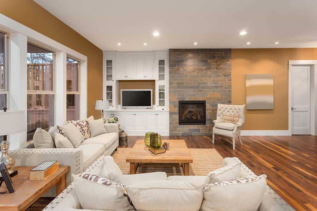 Beautiful living room interior with two couches at right angles, throw pillows, coffee table, built-in cabinets, hardwood floors and fireplace