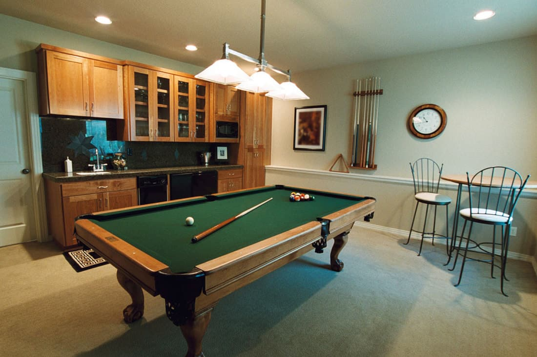 Billiard room with pantry on the side and hanging lamps above billiard table