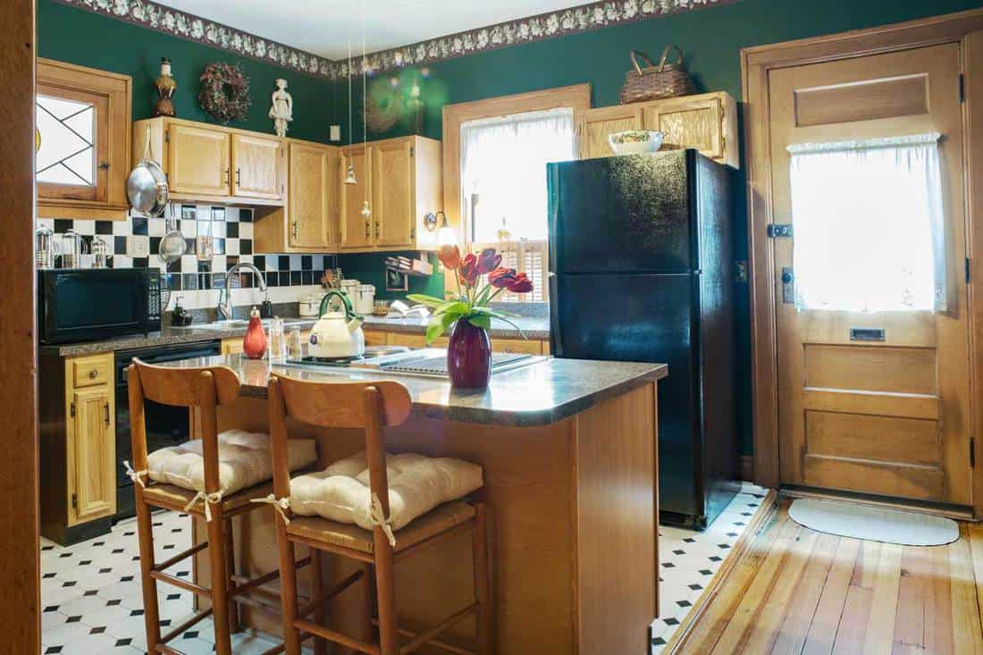 Black & white tile & flooring accent a green Victorian kitchen in hundred-year-old home.