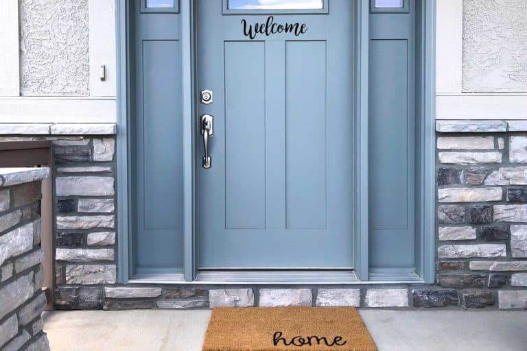 Blue front door of a modern home with welcome home sign, Should Your Front Door Be The Same Color Inside And Out?