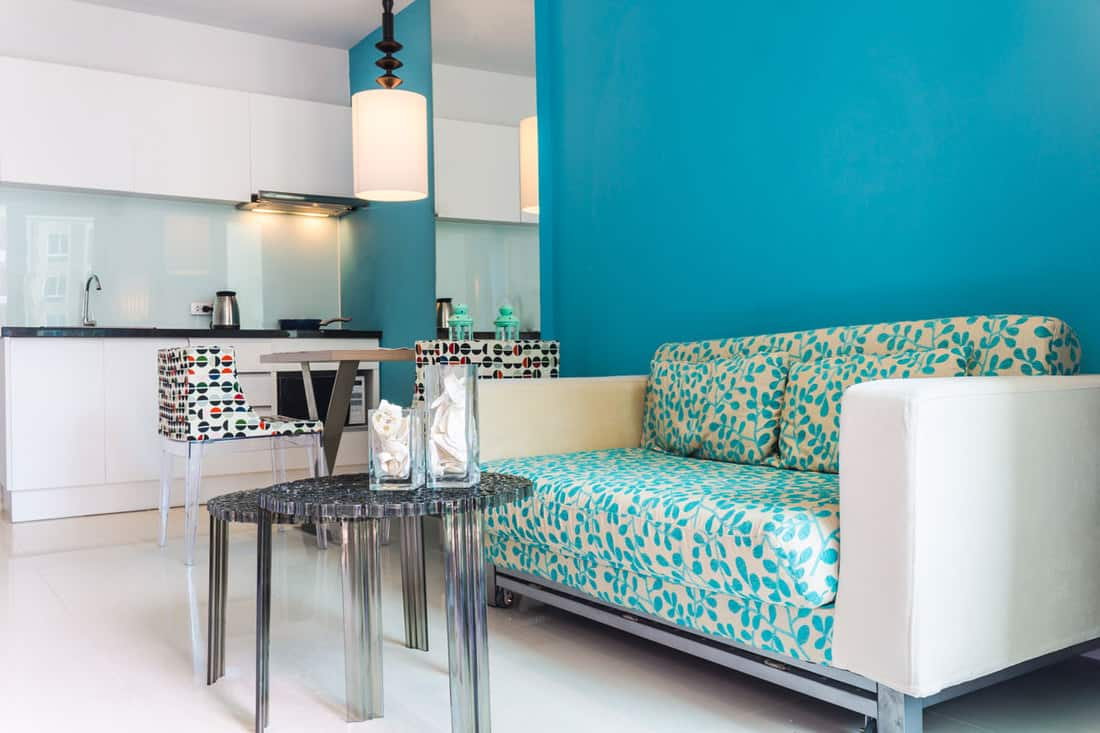 Blue wall living room with white couch and white colored flooring