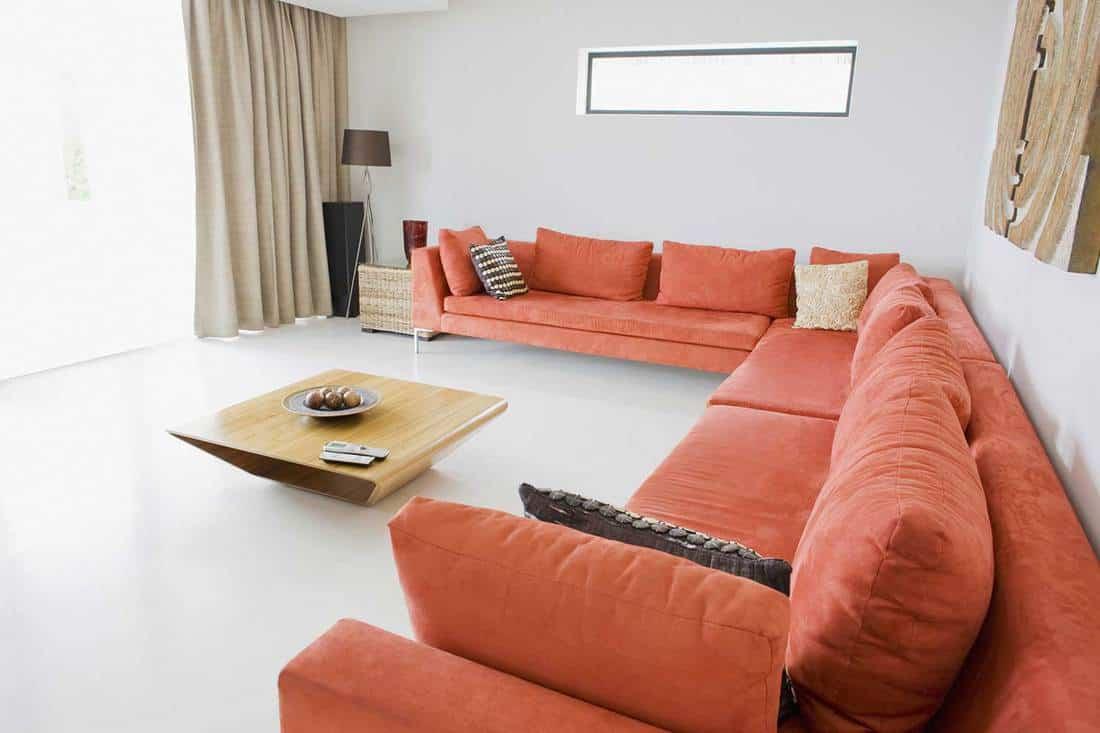 Bright living room in modern home with orange corner sofa