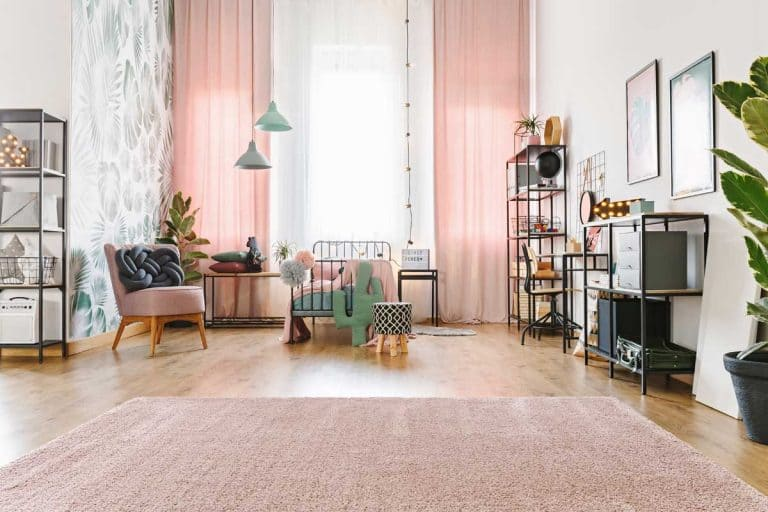 Bright spacious teenage girl room interior with metal bed, pink drapes and soft carpet on the floor, Do Curtains And Rugs Have To Match?