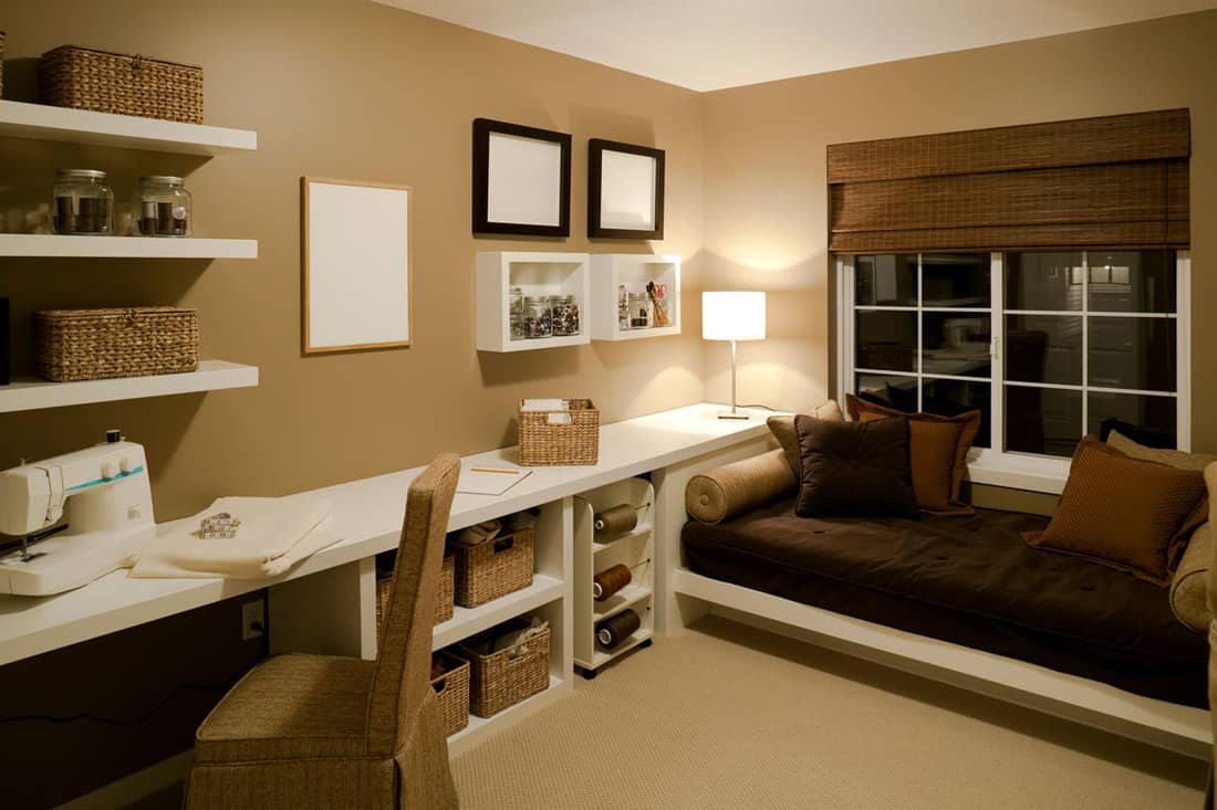 Brown colored walls with paintings and dividers for items and sewing table at the side