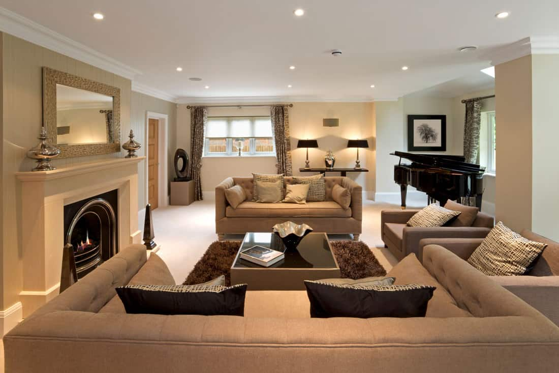 Brown couches with fireplace as centerpiece and white ceiling with ceiling lights